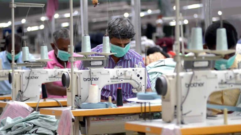 Ethical Fashion: Textile workers in PPE sewing garments.